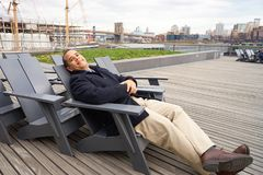Pier 15. NEW YORK - MARCH 17, 2016: man sit in the armchair at Pier 15 at daytime. Pier 15 is located east of South Street and FDR Drive in Lower Manhattan, New Royalty Free Stock Photography