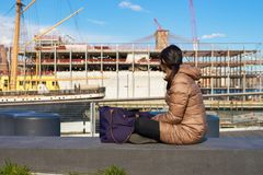 Pier 15. NEW YORK - MARCH 17, 2016: woman take a rest at Pier 15 at daytime. Pier 15 is located east of South Street and FDR Drive in Lower Manhattan, New York Stock Images