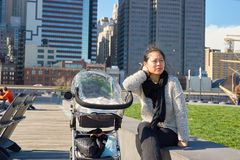 Pier 15. NEW YORK - MARCH 17, 2016: woman take a rest at Pier 15 at daytime. Pier 15 is located east of South Street and FDR Drive in Lower Manhattan, New York Stock Photo