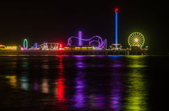 Pier at night. A night shot of the pier in Galveston, Texas.  The lights are reflected on the sea below Stock Photo