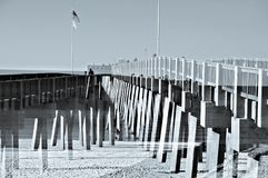 Pier at Ocean Double Exposure. A double exposure image of a fishing pier with a flag at the beach, tint added stock images