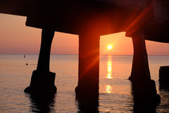 Pier on the ocean at sunrise Stock Images