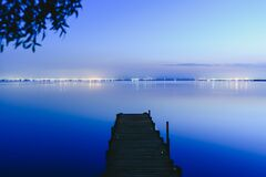 Free Pier On A Lake At Sunset With Calm Water And Reflections Of Relaxing Lights Stock Image - 170015801