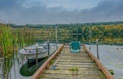 Pier op een meer met kleine boot royalty-vrije stock afbeelding