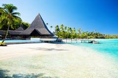 Pier op tropisch strand met verbazend water stock afbeeldingen