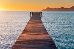 Pier in orange sunrise colors. Playa de Muro
