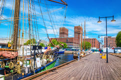 Pier Oslo Fjord with sailing ship, Norway. Beautiful City Hall viewed from the pier Oslo Fjord with a beautiful sailing ship in the foreground, Oslo, Norway Royalty Free Stock Photo