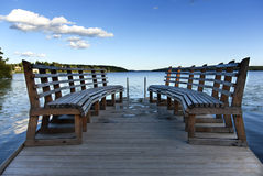 Pier over the lake. A pier with benches over a lake Royalty Free Stock Photos