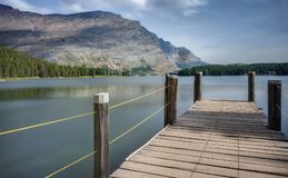 Pier over Swiftcurrent Lake in Glacier National Park. A Boat Dock and Fishing Pier Stretches into the Calm Waters of Swiftcurrent Lake at Glacier National Park Royalty Free Stock Image