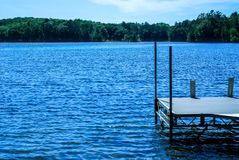 Pier overlooking the blue waters of Sawyer Lake in Norther Wisconsin. A pier overlooking the beautiful blue waters of Sawyer Lake near Silver Birch Ranch in royalty free stock photos