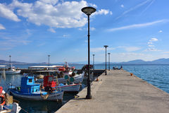 Pier in Paralia Politikon and small fishing boats, Greece. Paralia Politikon, Greece- Sept 24, 2016: Small fishing boats moored near pier at sunny warm evening stock image