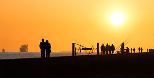 Pier with people fishing and walking. Hazy and yellow sunset from volcanodust in the air Stock Photos