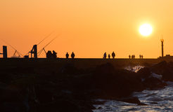 Pier with people fishing and walking. Hazy and yellow sunset from volcanodust in the air Royalty Free Stock Photos