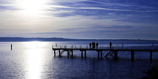 Pier with people silhouette. Pier on the sea with people on it, silhouetted against the strong sun Stock Photos
