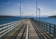 Pier without people on sunny day with the alps in background at Starnberg lake near munich in Germany royalty free stock photos
