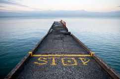 Pier perspective with yellow Stop label Stock Photo