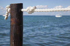Pier pile and rope overlooking ocean Stock Images