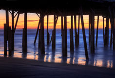 Pier Pilings Foundation Silhouette North Carolina. Pier pilings foundation supporting ocean boardwalk silhouetted against the ocean and sunlight in the pre-dawn Royalty Free Stock Photos