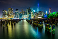 Pier pilings and the Manhattan skyline at night, seen from Brook Stock Photo