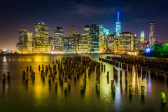 Pier pilings and the Manhattan skyline at night, seen from Brook Royalty Free Stock Photo