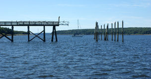 Pier with pilings and a sailboat in between Stock Photo