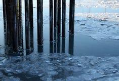 Pier pillars in icy water Stock Photos
