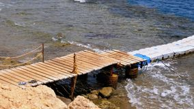 Pier or Pontoon on a Beach in Egypt over a Reef off the Coast of the Red Sea, Egypt. Rocky Beach in Sharm El Sheikh. Resort on Red Sea Coast. Daytime panoramic stock footage