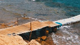 Pier or pontoon on a beach in Egypt over a Reef off the Coast of the Red Sea, Egypt. Rocky Beach in Sharm El Sheikh. Resort on Red Sea Coast. Daytime panoramic stock video