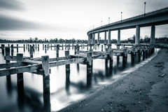 Pier posts in the Severn River and the Naval Academy Bridge, in Stock Photography