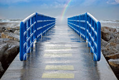 pier with rainbow and waves Royalty Free Stock Image