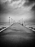 Pier in the rain. Artistic look in black and white. Stock Image