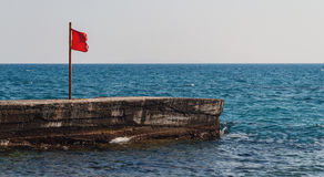 Pier with a red flag in the sea Royalty Free Stock Photography
