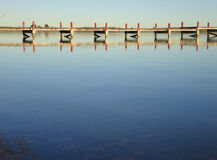 Pier reflected at calm lake Stock Images
