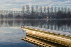 Pier. Reflecting pier on a winter morning royalty free stock photography