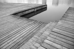Pier and reflection of buildings on river stock images