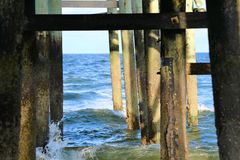 The wood beams of the ocean fishing pier frame the bright ocean sky stock photography