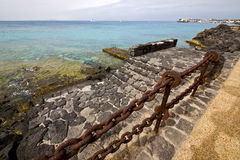 Pier rusty chain  water  boat yacht coastline and summer  lanzar Stock Photo