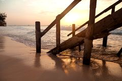 A pier on a sandy beach in the morning light stock photography