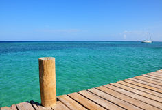 Pier and sea. Scenic view of post on wooden pier with calm turquoise sea in background under blue sky Stock Photography