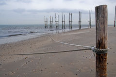 Pier in sea. With beach and pole with rope stock photography