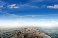Pier on the sea coast and fog over the water. stock photography
