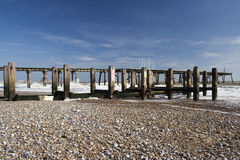 Pier and Sea Defences on Lowestoft Beach, Suffolk, England. Against a blue sky Stock Photo