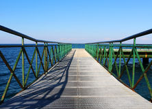 Pier at the sea with green railing. Photo of pier at the sea with green railing stock photos