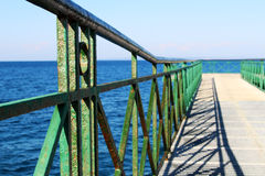 Pier at the sea with green railing. Photo of pier at the sea with green railing royalty free stock images