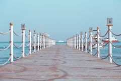 Pier on the sea leading to yacht royalty free stock image