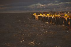 Pier in the sea in a storm royalty free stock photography