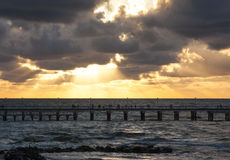 Pier and sea with waves at sunset sky background Royalty Free Stock Images