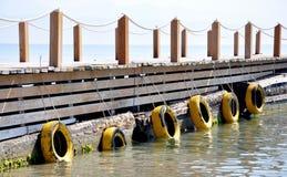 Pier in the sea. Wooden pier in the sea a tire Stock Photos