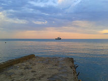 On the pier, seascape at sunset. Sochi coast, the boat in the blue sea Royalty Free Stock Image