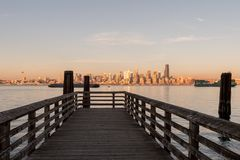 Pier in Seattle Bay with sunset light over downtown skyscrapers in the background, Washington, USA. stock photo